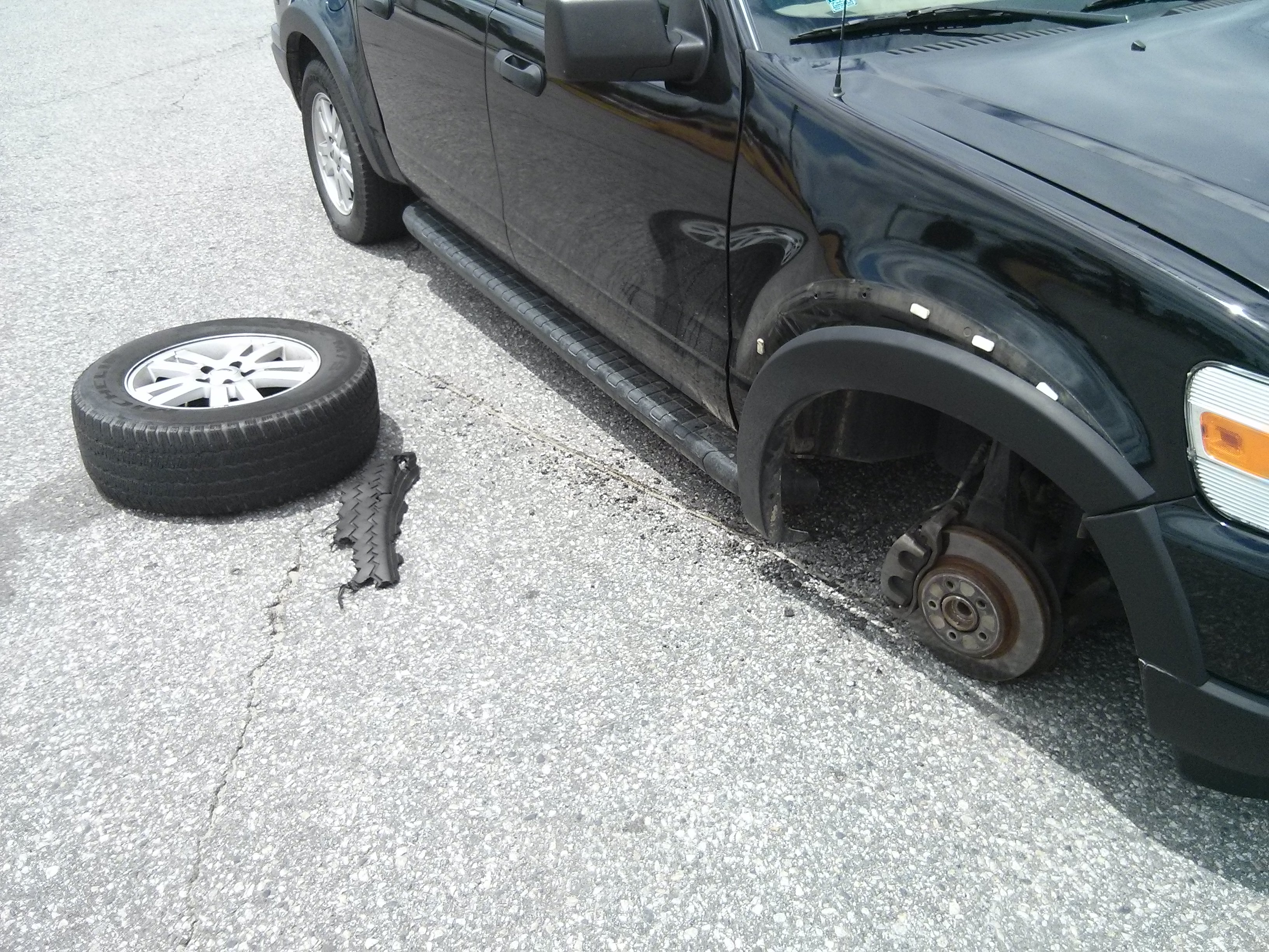 A dark truck missing a front right tire has left gouge marks in an asphalt surface, and the shredded front right tire sits on the ground beside it.