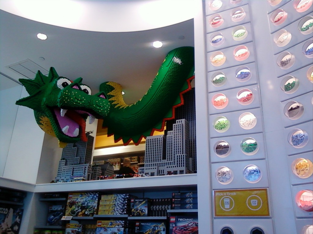a dragon made out of legos intertwined with ceiling at the Lego Store in NY.