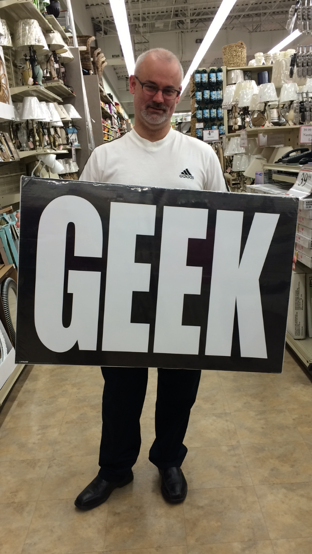 "Middle aged white male in soccer jersey holding very large poster that reads ""GEEK"" in a store."