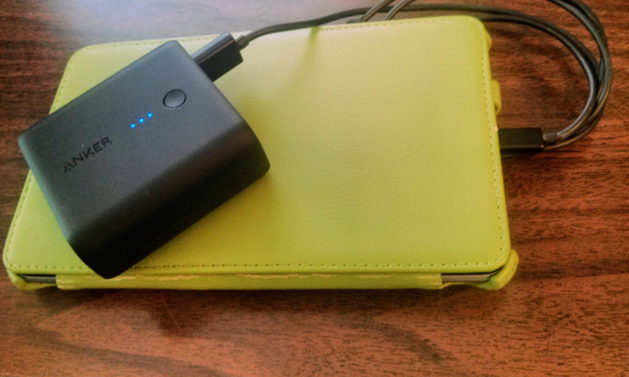 An Android tablet in a light green being charged by a portable battery on top of a desk.
