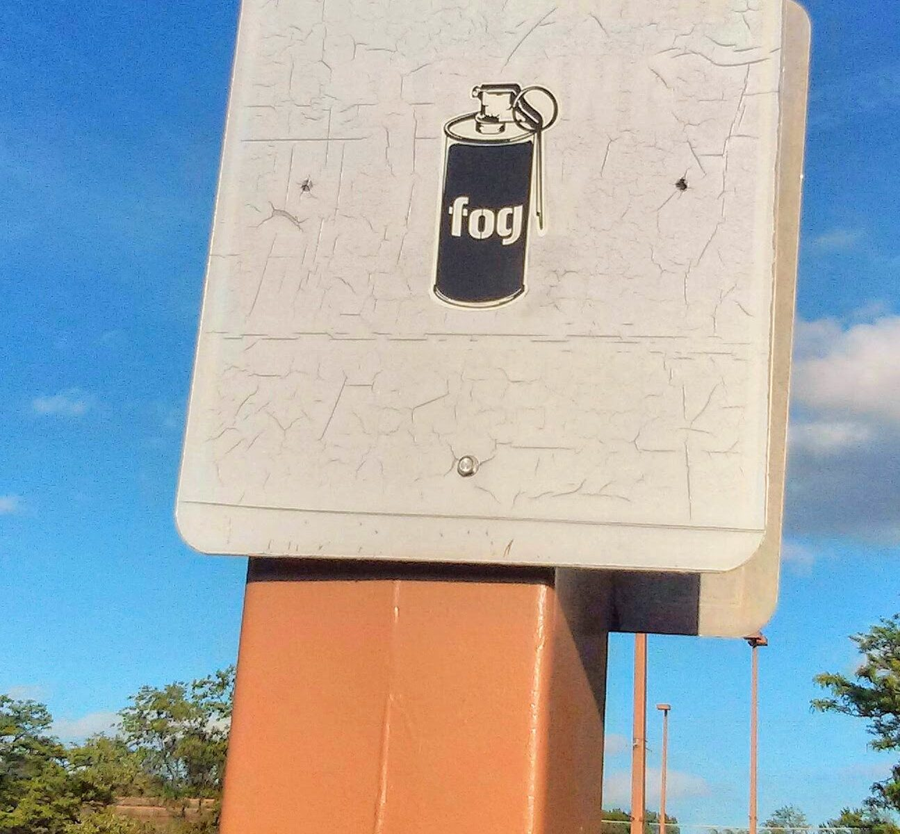 a sticker depicting a fog aerosol can has been placed on a faded out parking notice sign.