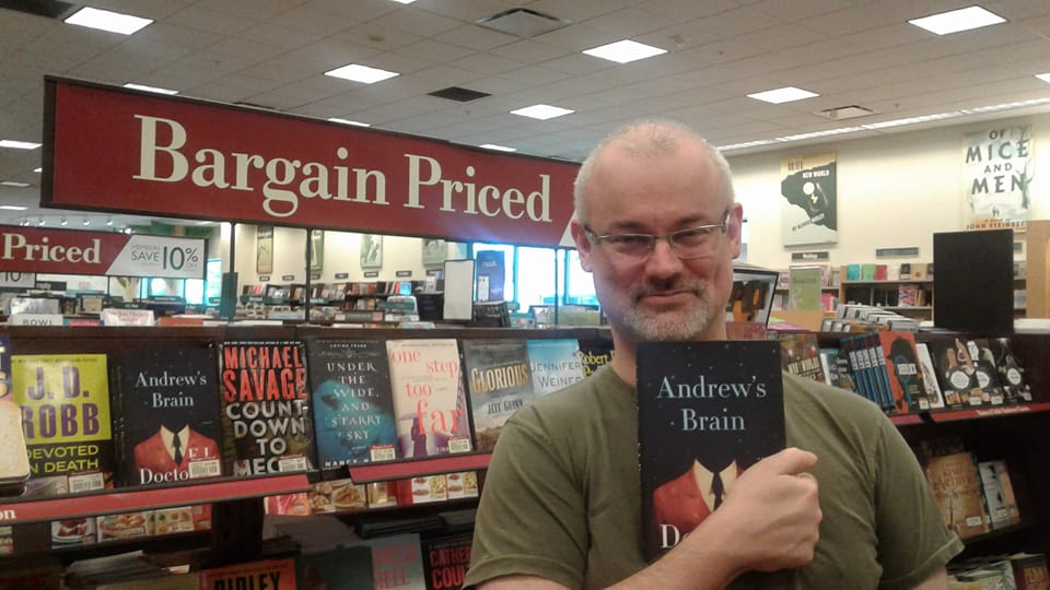 """Andrew Mills standing in front of a """"Bargain Priced"""" shelf of books, holding up a book titled, """"Andrew's Brain."""""""